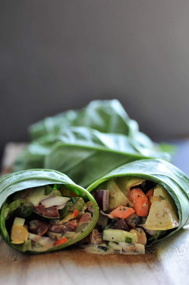 Salad with a thick and creamy tahini dressing, wrapped in a collard green leaf.