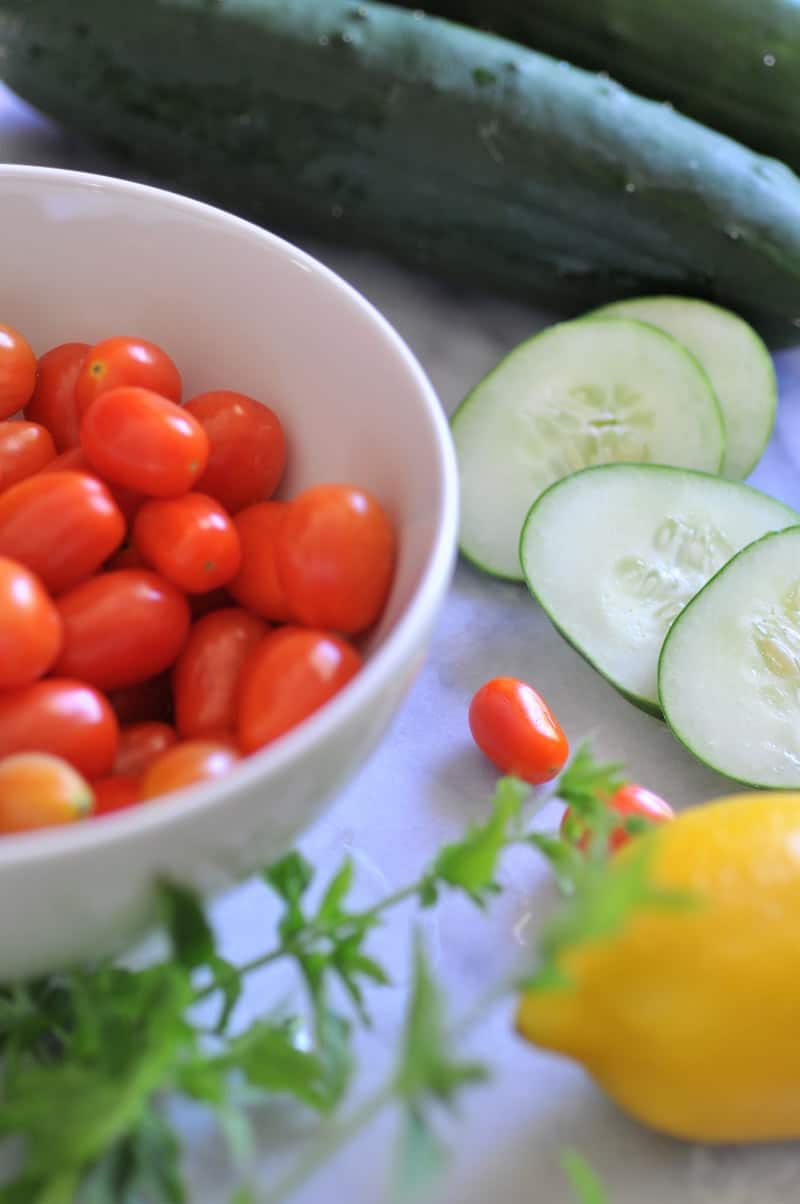 All the ingredients you'll need for a refreshing cucumber, tomato & mint salad with lemon dressing.