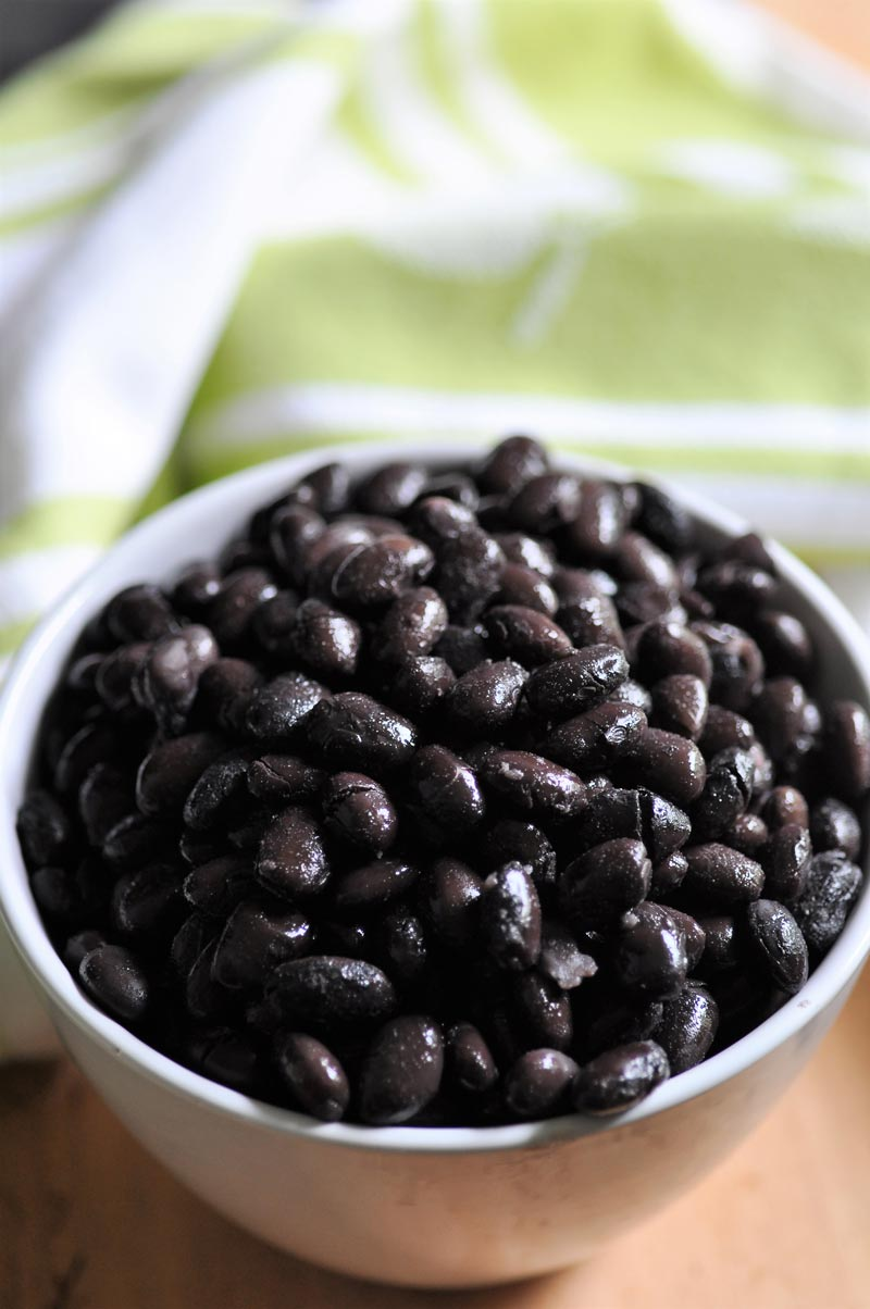 A white bowl with black beans.