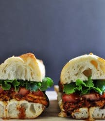 2 halves of an ELT (eggplant, lettuce & tomato) sandwich on a wood board.
