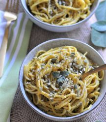 Pumpkin sage cream sauce smothered over spaghetti in a white bowl, sprinkled with pepitas and sage leaves.