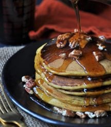 A stack of five vegan pumpkin pancakes on a black plate, sprinkled with pecans and a pat of butter. Syrup is being poured over them.