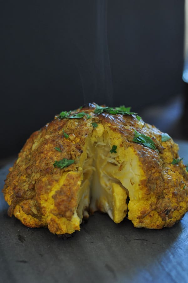 A steaming whole roasted cauliflower with a slice removed from it.