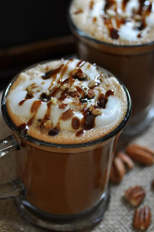 Homemade Vegan Maple Pecan Lattes in clear mugs with foamy milk and a drizzle of maple syrup and crushed pecans on top