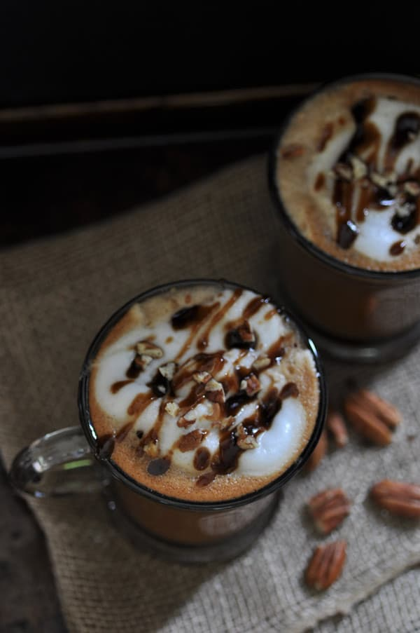 2 Maple Pecan Lattes in clear glass mugs on a burlap cloth with pecans scattered on it
