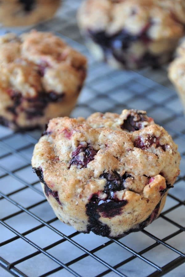 Vegan cranberry blueberry muffins cooling on a wire rack