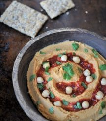 A wood bowl of spicy peanut chili hummus with chili sauce, cilantro, and whole chickpeas