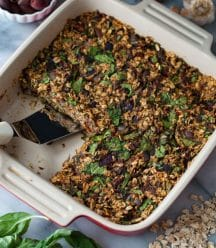 A red and white ceramic pan with baked savory oats, one piece is missing and there's a spatula in the pan