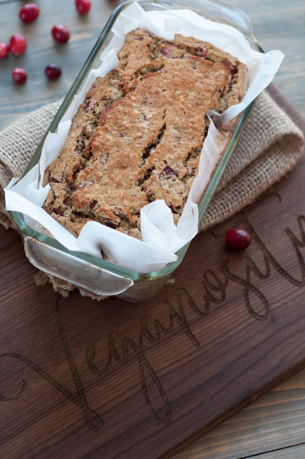 Vegan cranberry orange quick bread in a glass bread pan with parchment paper, sitting on a burlap cloth on a wood board.