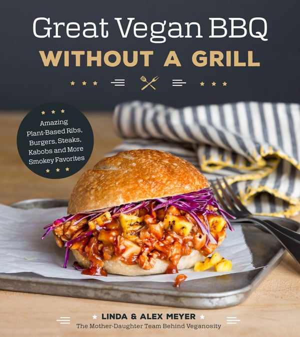 The book cover of Great Vegan BBQ Without a Grill. A vegan BBQ sandwich dripping with sauce and grilled pineapple on a piece of parchment paper on a silver tray with two forks and a blue and white striped napkin with yellow trim.