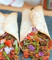 Greek Vegan Burritos from Vegan Burgers and Burritos Cookbook on a slate tray with hot sauce and onions in the background
