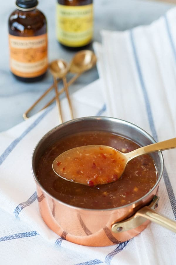 Spicy orange sauce in a copper pan with a gold spoon, sitting on a white and blue striped towel with Nielsen-Massey orange and lemon extract in the background.