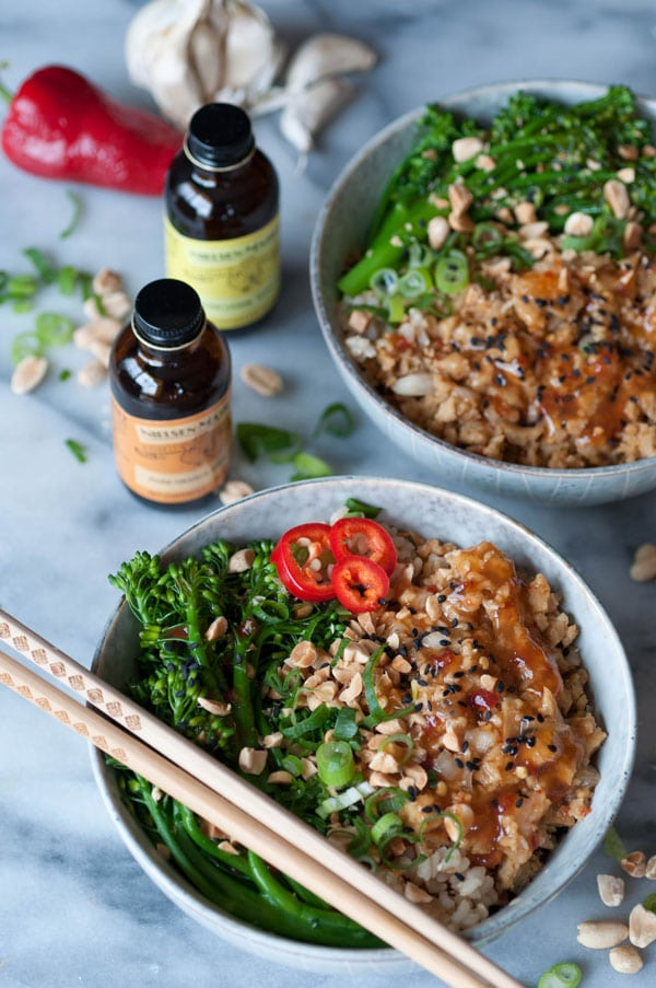 Vegan Ground Chik'n Bowls with chopsticks and another bowl behind it with bottles Nielsen-Massey Pure Orange and Lemon extract next to the bowls with peanuts, chopped green onion and a red pepper on a marble counter