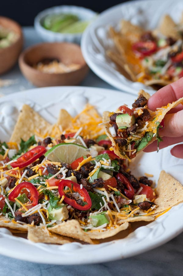 A hand holding a nacho from a white bowl of vegan nachos with another nacho bowl and a wood bowls of vegan cheese, and salsa in the background