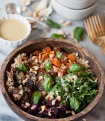 Roasted beets, squash, Brussels sprouts, and kale over brown rice in a wood bowl with chopped cashews and basil. Maple mustard dressing is on the side in a white dish with a stack of white bowls and gold forks on a marble counter.