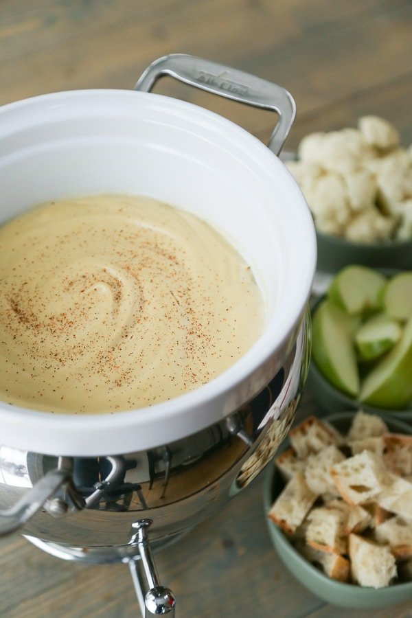 Vegan Fondue in a white fondue pot with bowls of bread, cauliflower, and apple slices on the side for dipping