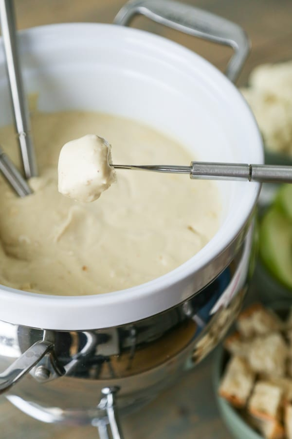 A white ceramic fondue pot filled with golden vegan cheese with a fondue fork dipping a piece of bread into the cheese