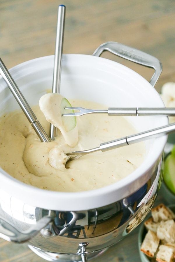 A white fondue pot filled with vegan cheese fondue with four silver fondue forks in the pot, one with a cube of bread and one with an apple slice, the other two are in the cheese
