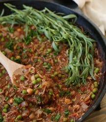 Tomato & Rice stew with chickpeas, peas, and Indian spices in an Iron skillet with a wooden spoon and fresh tarragon leaves on one side of the pan