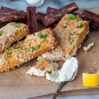 Vegan oven fried fish sticks with purple sweet potato fries and a spoon of tarter sauce and a lemon wedge.