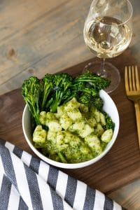 Pesto Gnocchi with Rapini a glass of wine, a gold fork, and a wood cutting board