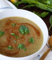 Spicy green soup in a white bowl with basil leaves and swirls of paprika on top. Sitting on a blue and white striped towel with a gold spoon and parsley and lemon on the side.