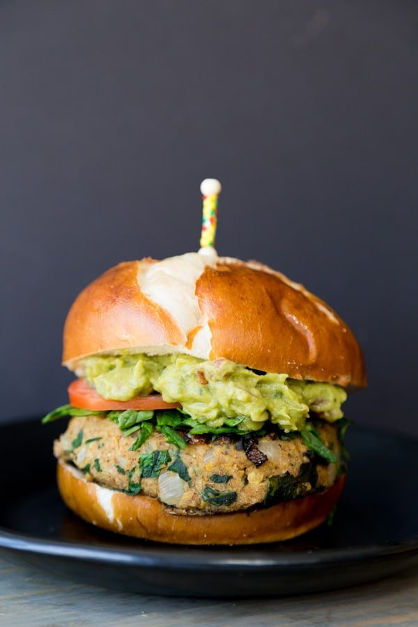 A thick spinach burger patty between a pretzel bun, shredded fresh spinach, sliced tomato, and mashed avocado on a black plate with a yellow and red toothpick stuck on the top of the bun