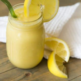 A mason jar filled with vegan lemon slushy with a slice of lemon on the glass and a green straw with lemon wedges and a white napkin on a wood table