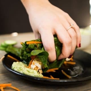 Tofu wrap being grabbed by hand and dipped into tzatziki sauce