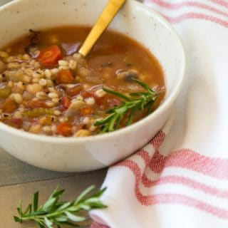 Italian Lemon Rosemary Barley Soup with a red and white napkin, rosemary, and on top of a wood cutting board