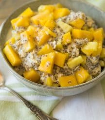 mango pineapple overnight oats in a grey bowl with a green napkin behind it and a silver spoon