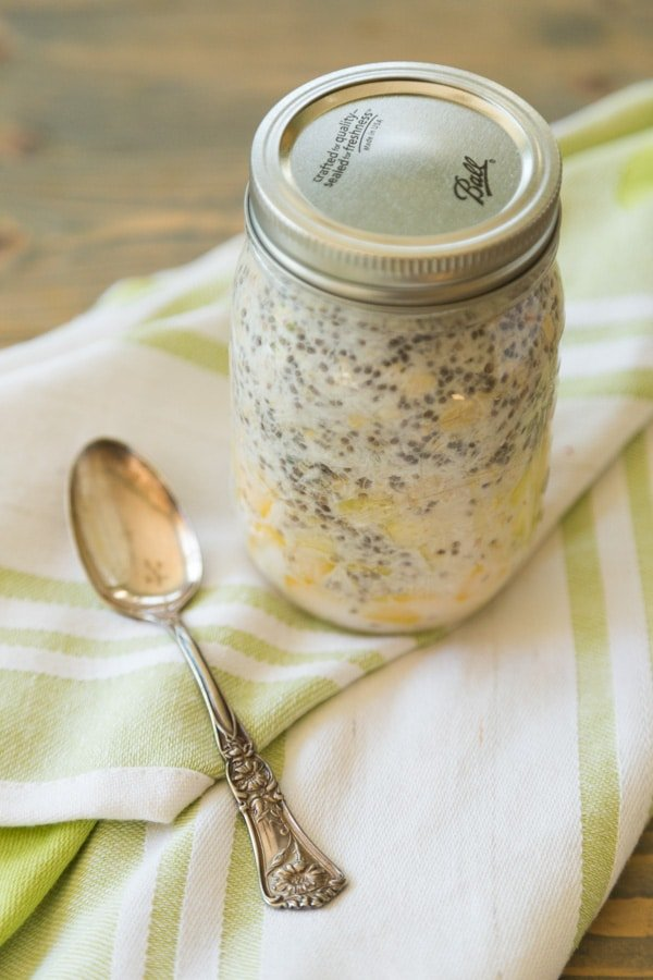 mango pineapple coconut overnight oats to go in a mason jar with a silver spoon next to it