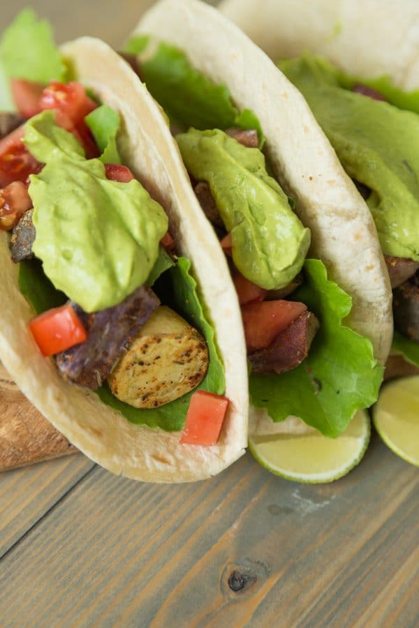 Three tacos filled with potatoes, peppers and a dollop of avocado sauce on top