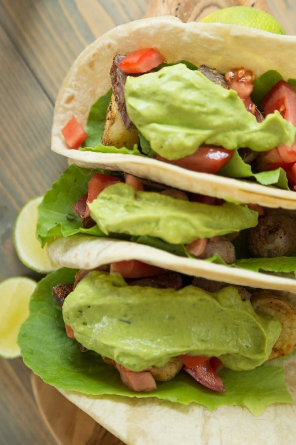 Three potato tacos with tomato and a large dollop of avocado lime sauce on a wood board with lime wedges next to them
