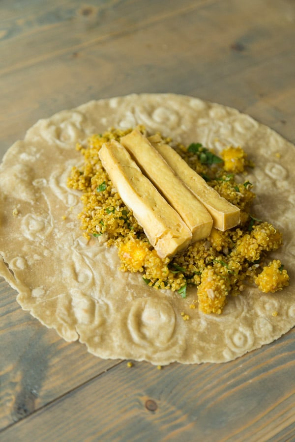 A tortilla on a wood board with curried quinao, mango and tofu about to be made into one of our curry tofu wraps
