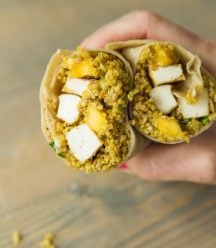 A hand holding a curried quinoa, mango and tofu wraps over a wood board