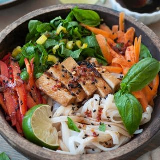 A wood bowl with cold sesame noodles and slivered bell peppers, carrots and yellow chard with basil and a lime wedge and a small white bowl of sesame dressing in the background with stacked blue plates and chopsticks