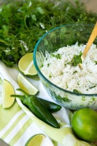 A glass bowl filled with cilantro lime rice on a green and white towel with a gold spoon in the bowl with jalapeno peppers, limes and a bunch of cilantro around it.