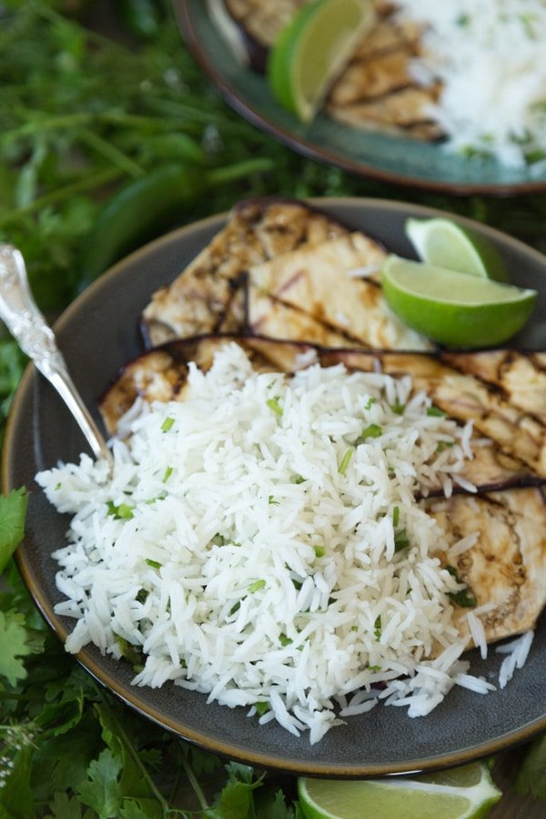 A pile of cilantro lime rice with grilled eggplant on a dark plate with a silver fork and lime wedges
