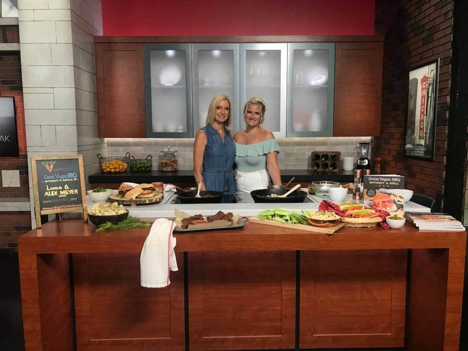 Linda and Alex at WGN News studios in front of the recipes they made for the Veganosity Cookbook; Great Vegan BBQ Without a Grill