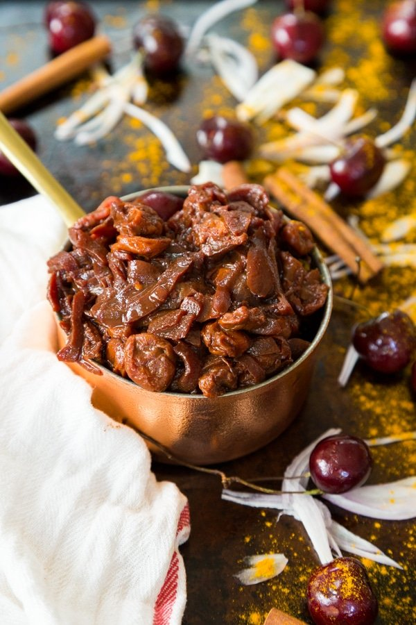 Cherry Onion Confit in a copper pot with turmeric, cinnamon sticks, cherries, and slivered onions in the background