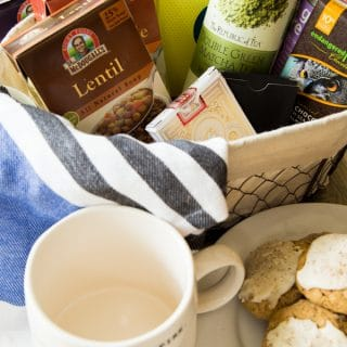 A wire basket with tea, snacks, and soup and a plate of cookies and a white mug next to it