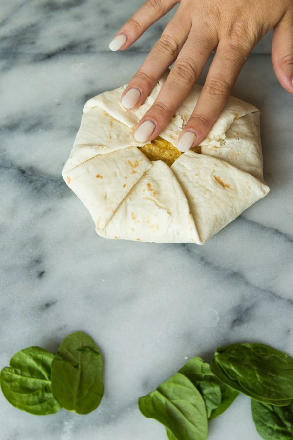 A perfectly folded crunchwrap supreme on a marble surface