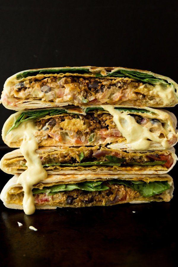 Four halves of vegan crunchwrap supremes stacked on to of each other with vegan cheese sauce dripping down the sides.