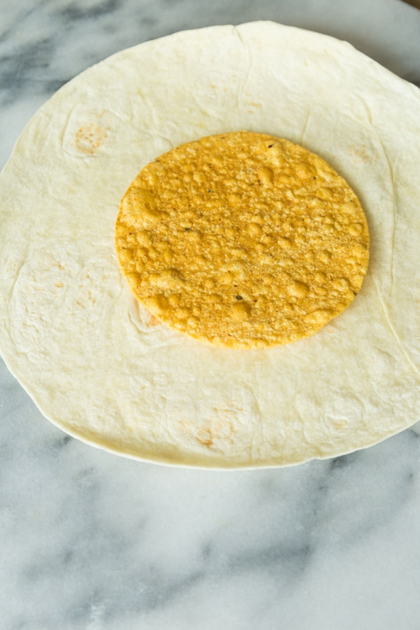 A large flour tortilla with a corn tostada shell in the center on a marble surface