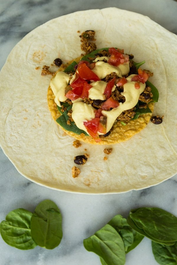 A large flour tortilla with a tostada shell in the center piled with baby spinach leaves, vegan taco filling, vegan cheese sauce and diced tomatoes