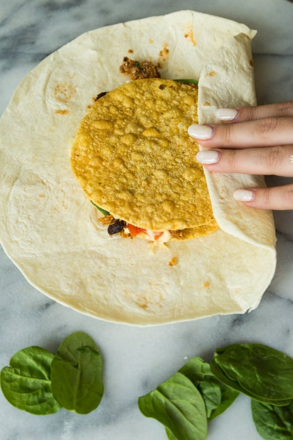 Folding the flour tortilla over the center of a crunchwrap supreme