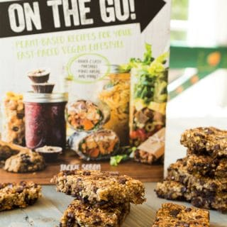 Vegan Yack Attack On the Go Cookbook standing on a table with Vanilla Chip Buckwheat Bars scattered on the table in front of it.