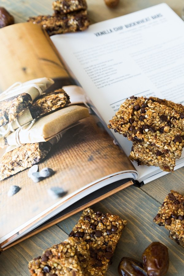An open page of vanilla chip buckwheat bars in the Vegan Yack Attack On the Go cookbook and the cooked bars scattered next to the book