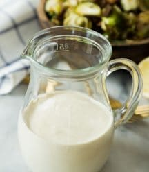 Caesar Dressing in a glass container with the brussels sprout salad behind it